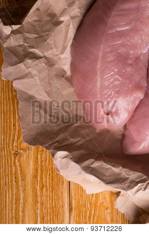 Raw chicken breasts lying on a sheet of oven paper, topped ready to be cooked for dinner