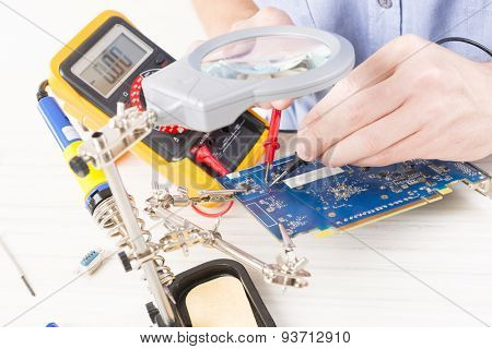 Serviceman checks PCB with a digital multimeter in the service workshop