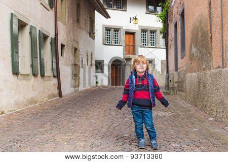 Outdoor portrait of a cute little boy in an old town