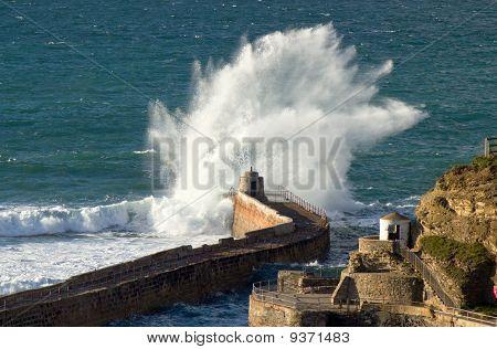 Big wave splash on Portreath pier Cornwall UK.