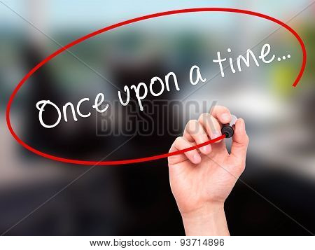 Man Hand writing Once upon a time... with black marker on visual screen.