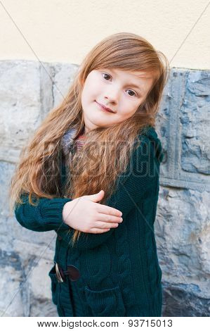 Outdoor portrait of a cute little girl wearing green knitted cardigan