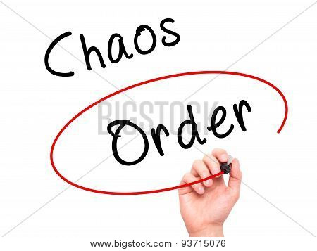 Man Hand writing and Choosing Order instead of Chaos with black marker on visual screen.