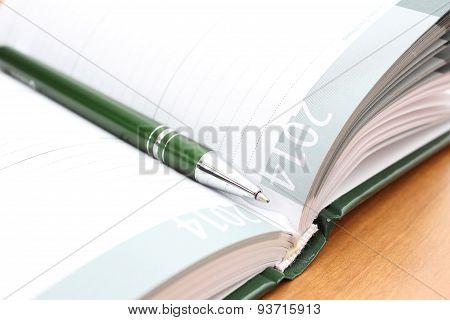 Green Pen Lying On Open Organizer On A Desk