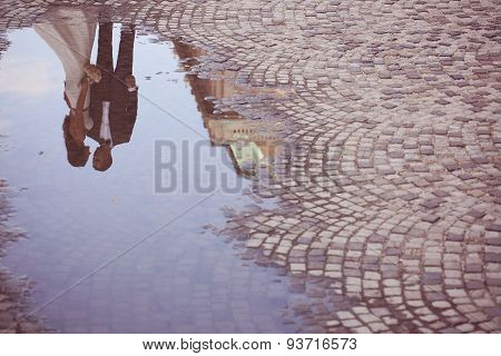 Bride And Groom Reflected In Slop On Paved Road