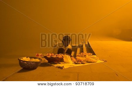 VARANASI, INDIA - 20 FEBRUARY 2015: Street vendor makes puja flower and candle light in early morning on foggy Varanasi ghats.