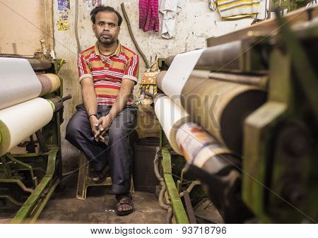VARANASI, INDIA - 21 FEBRUARY 2015: Worker sits on chair next to textile machine in small factory.