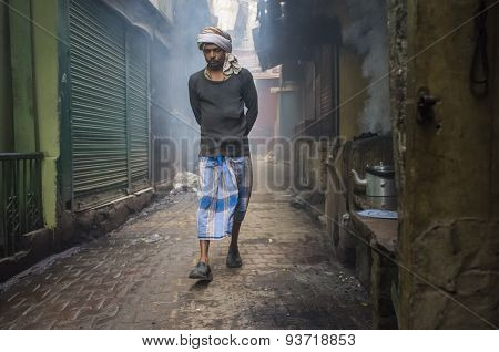 VARANASI, INDIA - 20 FEBRUARY 2015: Man walking through street filled with smoke. Coal ovens are used as source of heat for making milky tea.