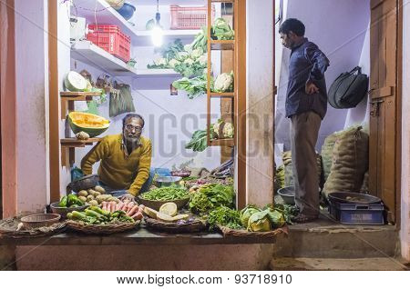 VARANASI, INDIA - 19 FEBRUARY 2015: Grocer sitting on ground with customer standing in doorway small vegetable shop on street market. Traditional traders are core part of Indian culture.