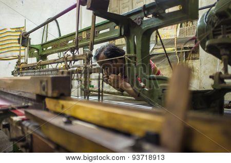 VARANASI, INDIA - 21 FEBRUARY 2015: Worker repairs textile machine in small factory.