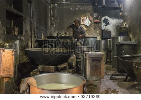 VARANASI, INDIA - 19 FEBRUARY 2015: Indian cook makes last meal after long work day.