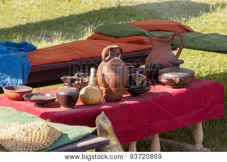Clay Utensils On Table With A Red Cloth Coverings