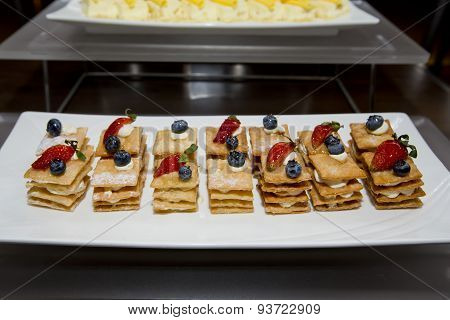 Stack Of Crispy Pancake With Banana Slice Topping Of Strawberry, Blueberry And Sugar
