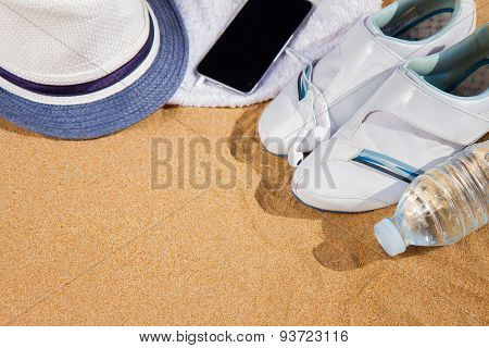 white sneakers with hat in sand