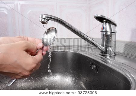 Women's Hands Washing The Spoon