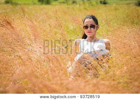 Girl in sunglasses in the field.