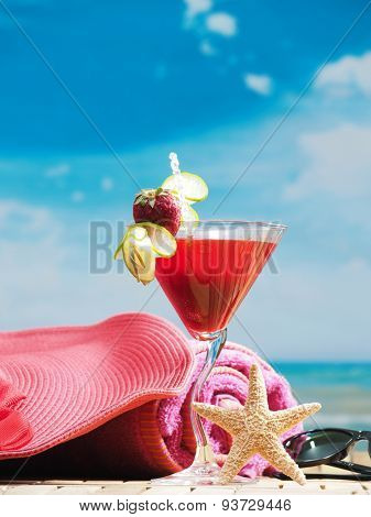 A tropical drink sitting on sand with a sky background, tropical drinks