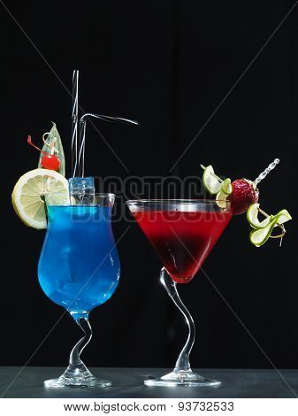 Two cocktails blue and red isolated over black