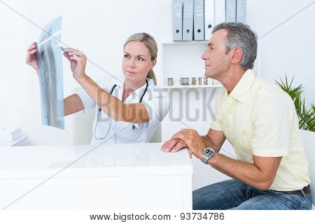 Doctor showing Xrays to her patient in medical office