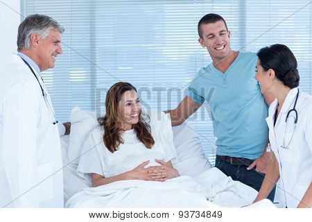 Future parents talking with smiling doctors in hospital room