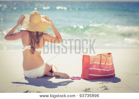 Back turned blonde in swimsuit sitting on the beach and looking the horizon