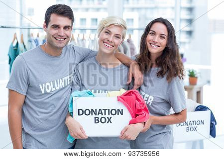 Happy volunteers friends holding a donation box