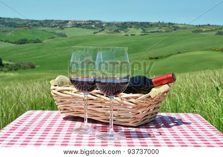 Red wine on the chequered cloth against Tuscan landscape. Italy