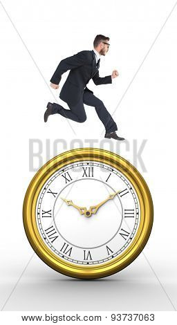 Geeky young businessman running mid air against golden clock