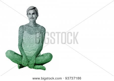 Smiling blonde woman sitting on the floor against astro turf surface