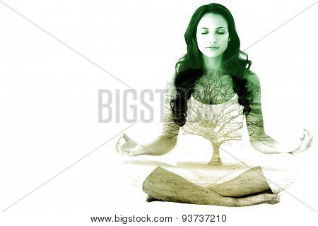 Pretty brunette doing yoga against tree in showy field