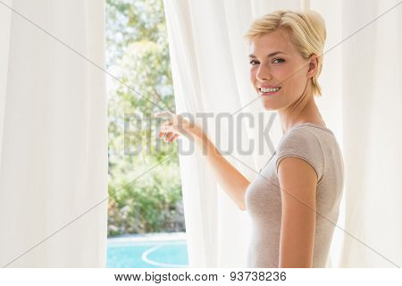 Portrait smiling blonde woman showing outside at home