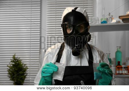 Chemists holding plastic bag with blue methamphetamine and money in laboratory