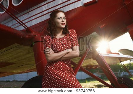 pin-up lady sitting on airplane wheel in red dress