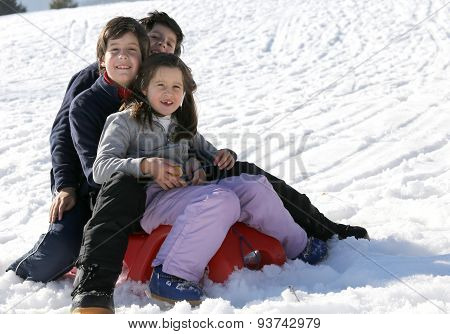 Three Smiling Siblings Over The Sled In Winter