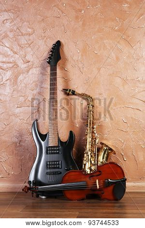 Electric guitar, saxophone and violin on brown wall background