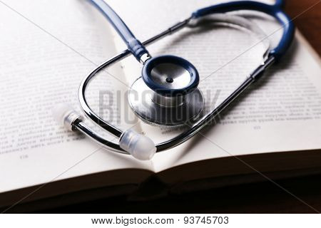 Stethoscope on book on wooden table, closeup