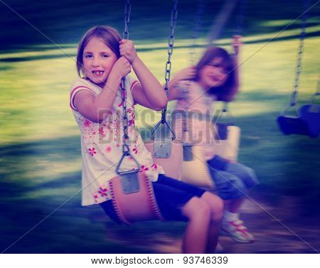 Little girls playing on swing set at a park instagram style