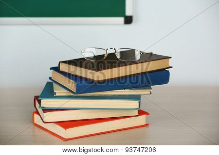 Heap of books and glasses on table in class