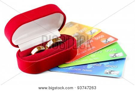 Golden wedding rings and credit cards, isolated on white. Marriage of convenience concept