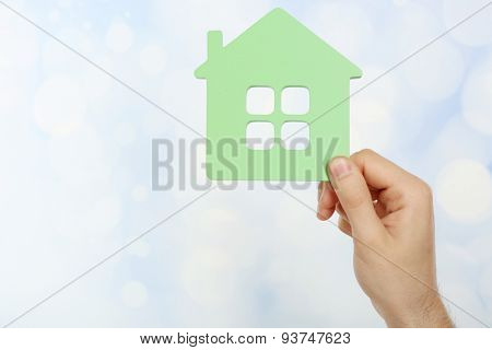 Female hand holding house on light blurred background