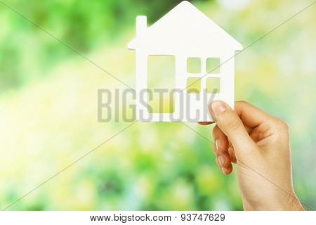 Female hand holding house on green blurred background