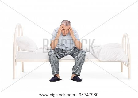 Studio shot of a frustrated senior sitting on a bed in his pajamas and looking down isolated on white background