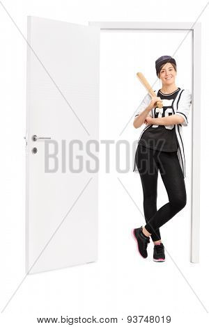 Full length portrait of a young woman holding a baseball bat and leaning against the frame of an open door isolated on white background