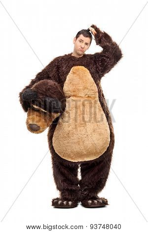 Full length portrait of a confused young man in a bear costume scratching his head and looking at the camera isolated on white background