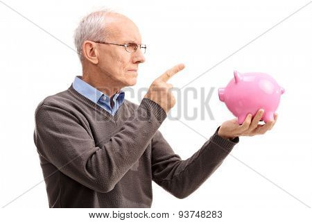 Studio shot of an angry senior scolding a piggybank isolated on white background