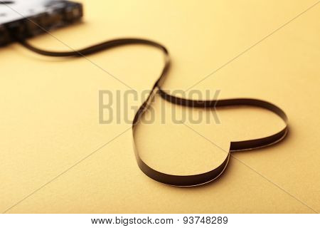Audio cassette with magnetic tape in shape of heart on yellow background