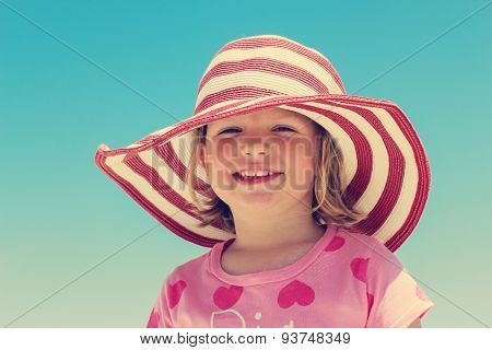 Beautiful Little Girl In The Striped Hat On The Beach. The Image Is Tinted.