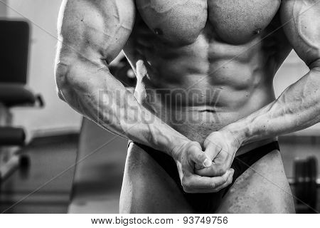 Handsome and strong man with beautiful body doing exercises in gym
