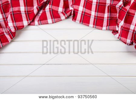 Top view of checkered kitchen towels on wooden table. Free space for your information