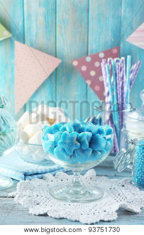 Sweet candies in glassware on wooden background